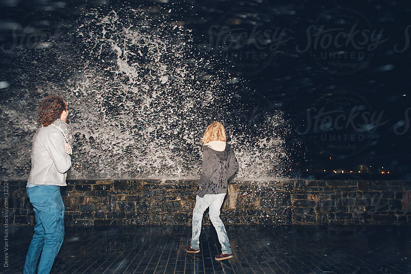 Two friends crouching run away from the water splashing up against the harbour walls by Denni Van Huis for Stocksy United