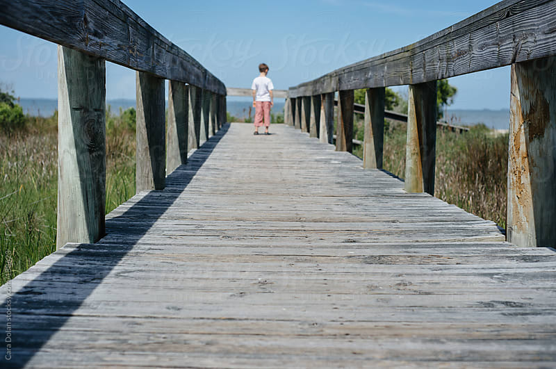 Boy stands at the end of a wooden boardwalk leading to a beach by Cara Dolan for Stocksy United