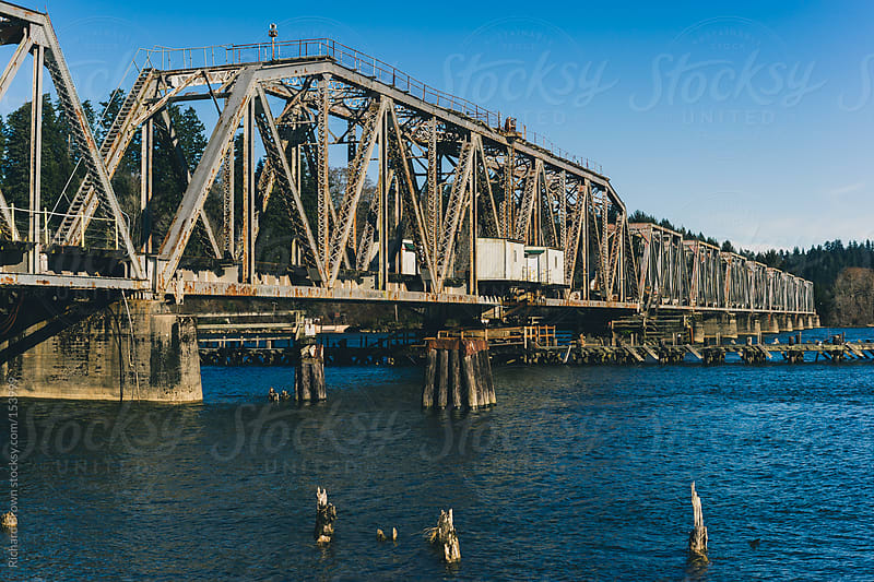 Truss bridge over blue water by Richard Brown for Stocksy United