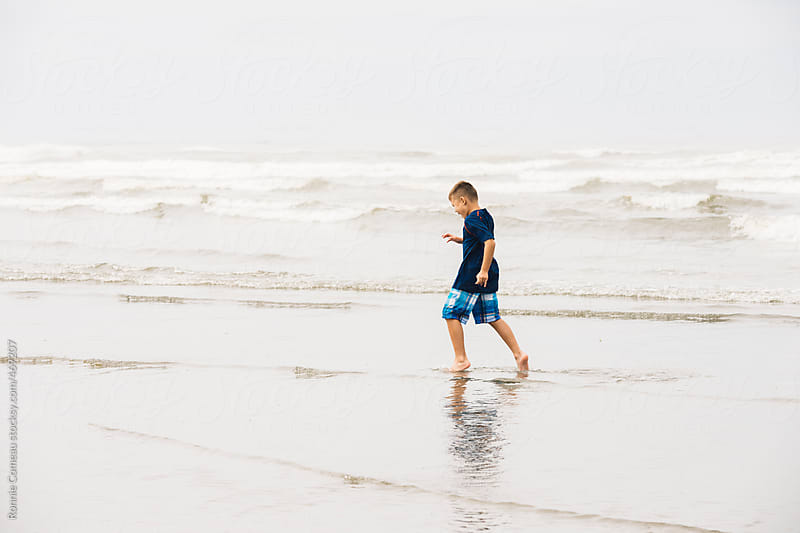 Boy Running In Water At The Beach by Ronnie Comeau for Stocksy United