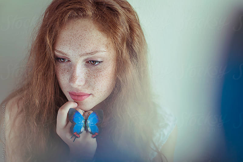 Beautiful young redhead woman with freckles holding a blue butterfly by Maja Topcagic for Stocksy United