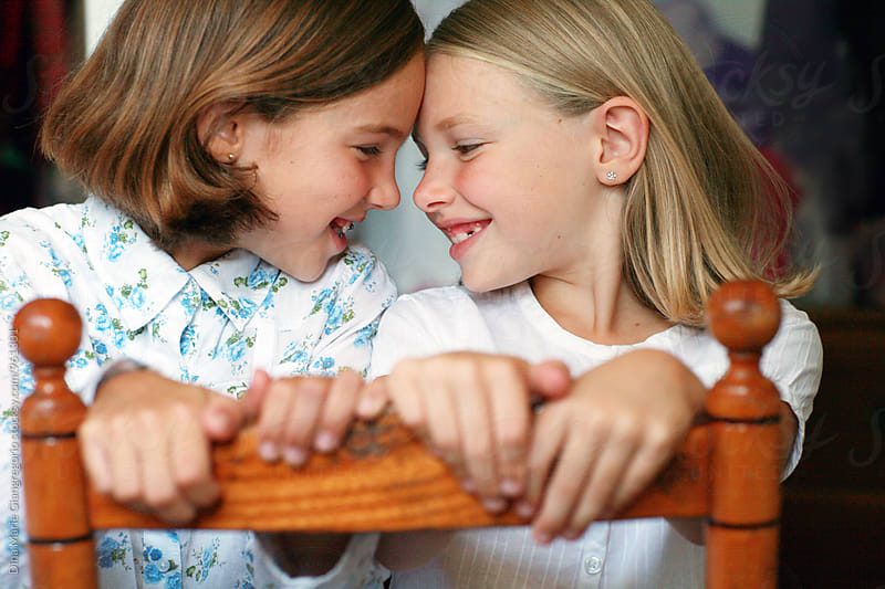Two Sisters Sitting on a Chair Face To Face by Dina Giangregorio for Stocksy United