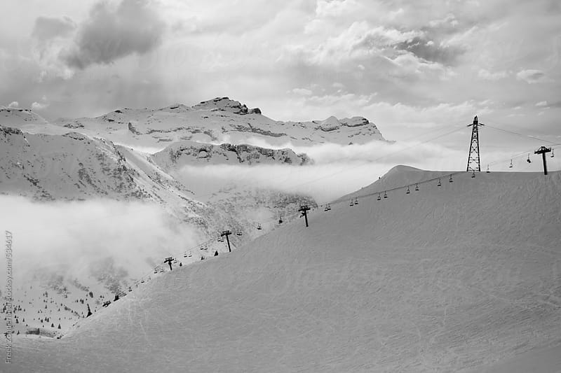 Mountain view with snow and clouds by Freek Zonderland for Stocksy United