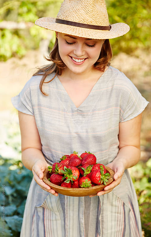 Woman farmer holding fresh picked strawberries on organic farm by Trinette Reed for Stocksy United
