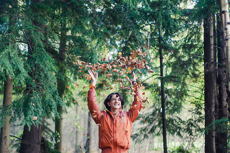 Teenage boy in orange jacket throwing autumn leaves in the air by Cindy Prins for Stocksy United