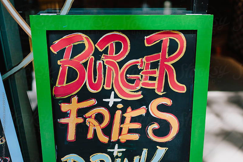 The words burger and fries drawn on a chalk board.  by Kristen Curette Hines for Stocksy United