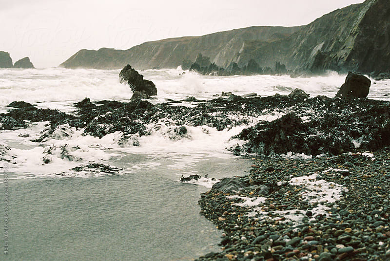 A wild and foamy beach in bad weather by Helen Rushbrook for Stocksy United