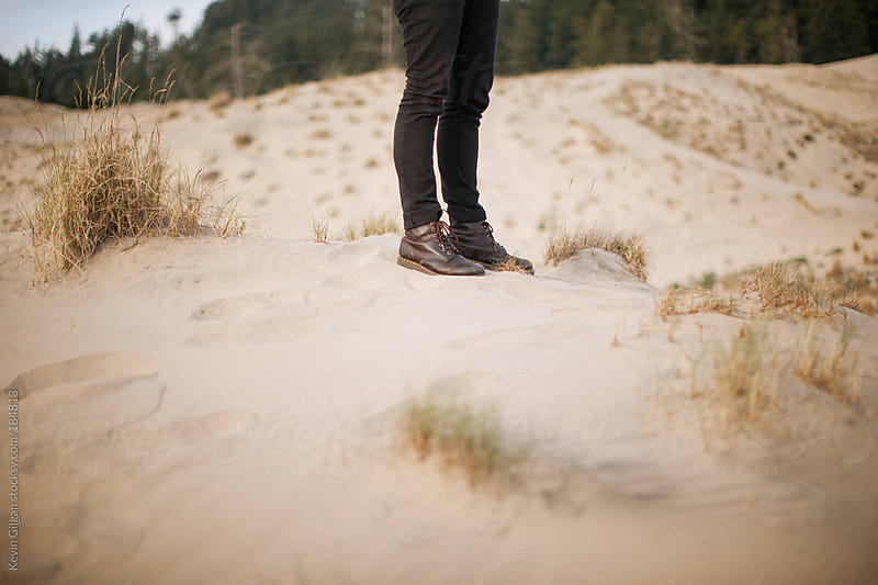 Man Stands in Sand Dunes by Kevin Gilgan for Stocksy United