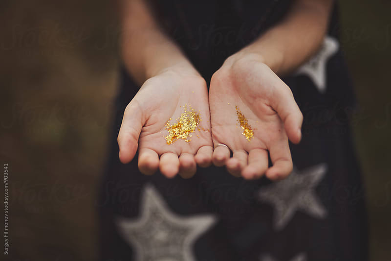 Palms of the young girl in golden spangles by Sergey Filimonov for Stocksy United