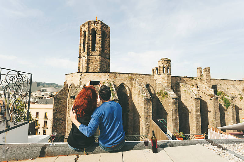 Beautiful couple taking photos and drinking wine on the rooftop in front a romanic church. by BONNINSTUDIO for Stocksy United