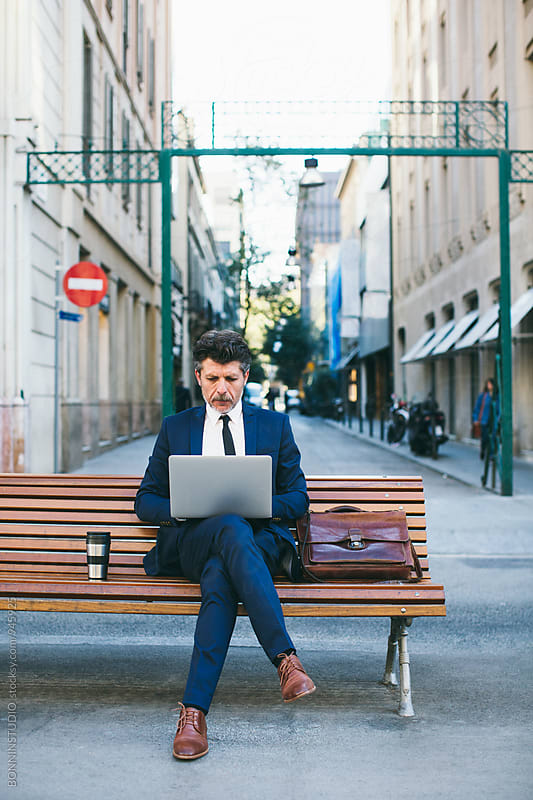 Mature businessman working on laptop sitting on a bench. by BONNINSTUDIO for Stocksy United