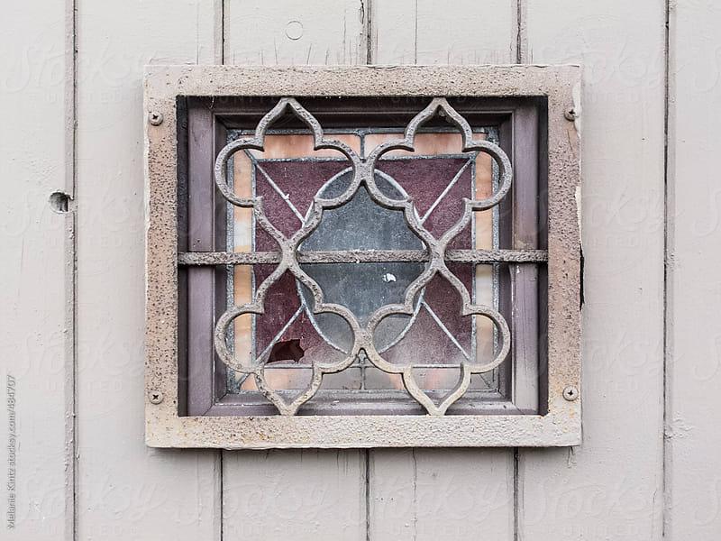 Small broken window behind protective metal bars by Melanie Kintz for Stocksy United