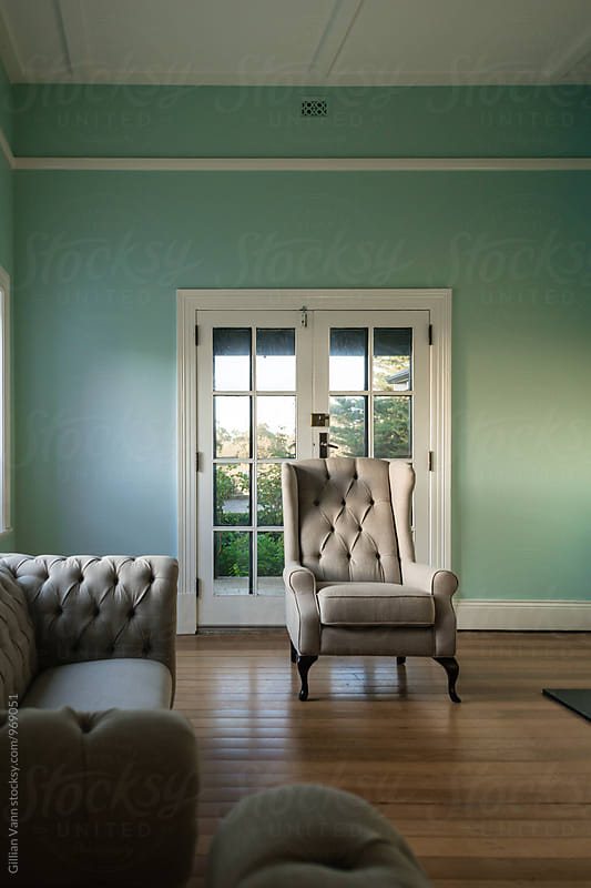 sitting room with linen wingback chair and sofa by Gillian Vann for Stocksy United
