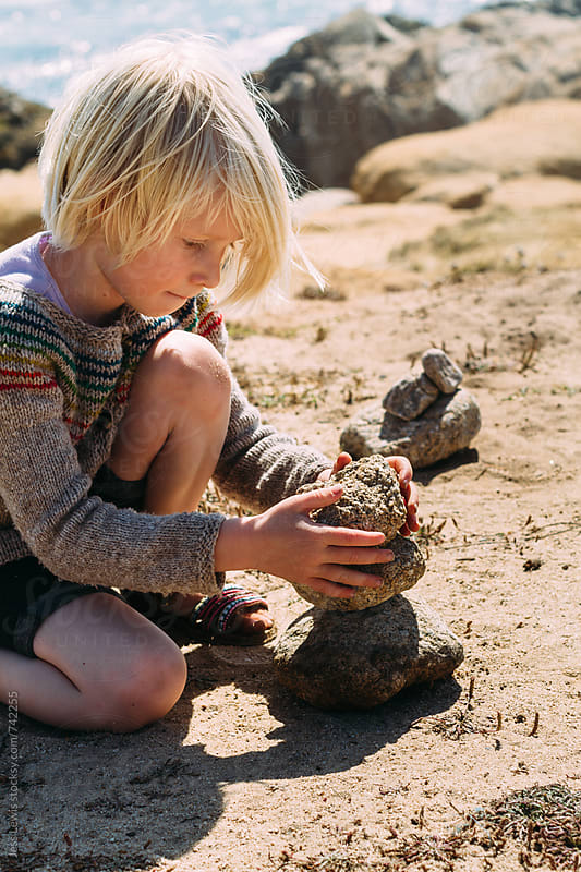 child concentrating on stacking stones by Jess Lewis for Stocksy United