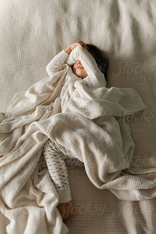 Young girl covering her face in the morning, covered in blankets by Amanda Worrall for Stocksy United