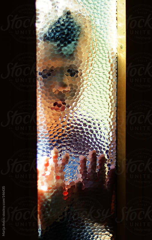 Boy behind frosted glass by Marija Anicic for Stocksy United