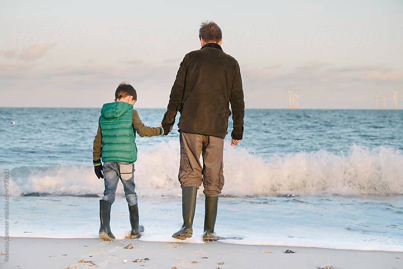 Father and child hold hands as they stand in the sea by Rebecca Spencer for Stocksy United