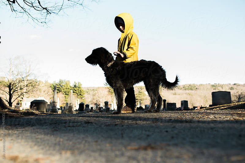 little boy walking his black dog by Léa Jones for Stocksy United