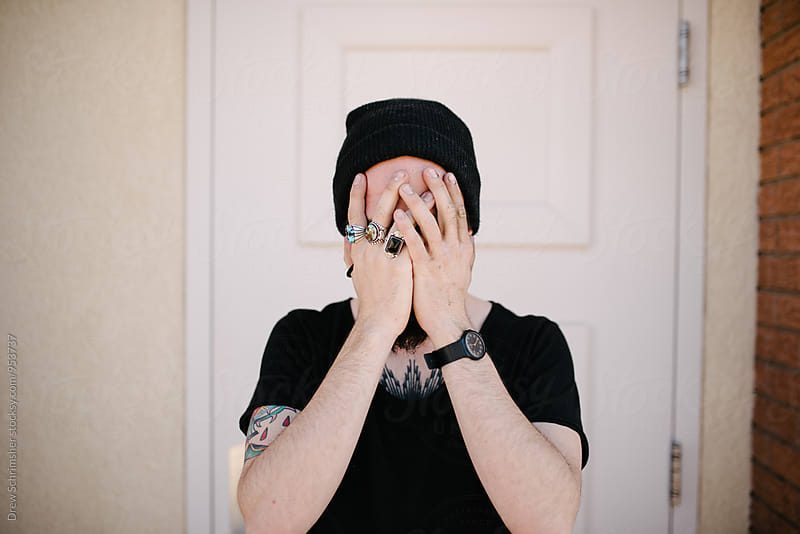 Young man covers face with hands  by Drew Schrimsher for Stocksy United
