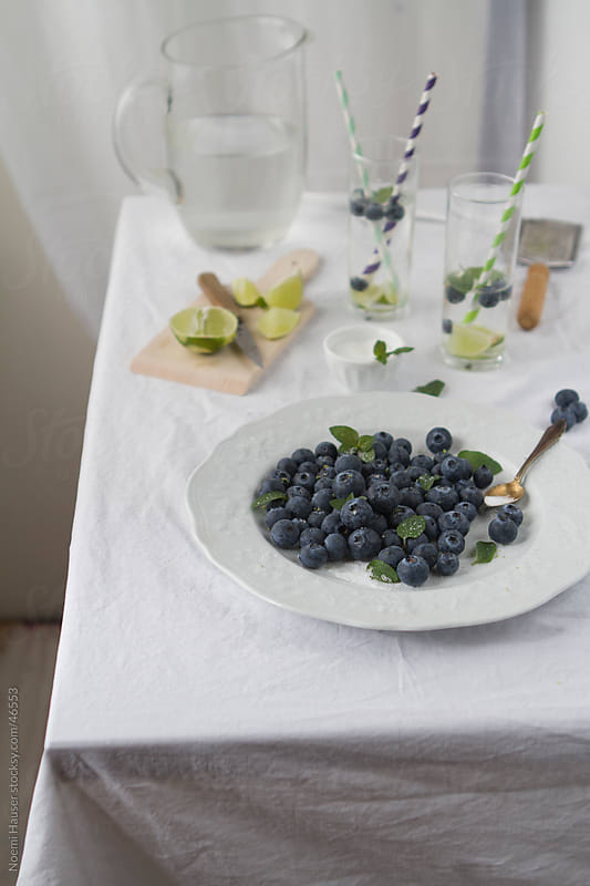 Blueberries on white plate with lime lemonade by Noemi Hauser for Stocksy United