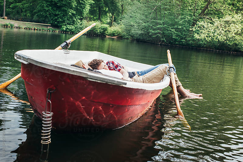 Young Heterosexual Couple Cuddling and Napping in Red Rowboat on Lake by VISUALSPECTRUM for Stocksy United