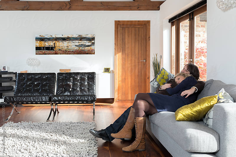Couple snuggling together in a modern living room. by Paul Phillips for Stocksy United