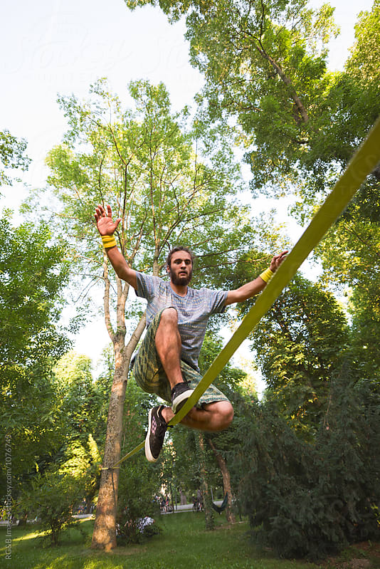 Young man balancing while doing tricks on slackline by RG&B Images for Stocksy United