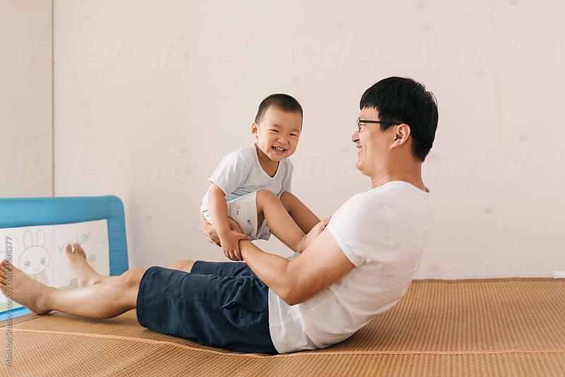 Chinese young father and his toddler son playing on bed by MaaHoo Studio for Stocksy United