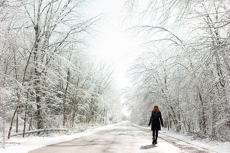 Redhead Woman Walking on Icy Road In Winter With Snow by JP Danko for Stocksy United