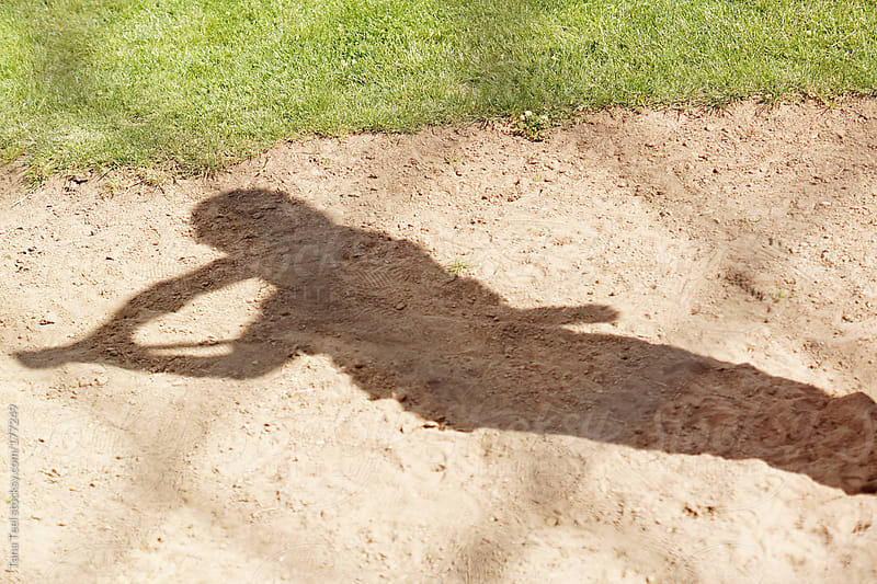 The shadow of a baseball player swinging a bat by Tana Teel for Stocksy United