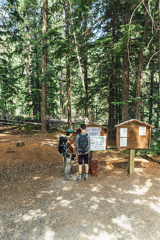 Two hikers at a Trailhead Self-Service Pay station by Adam Nixon for Stocksy United