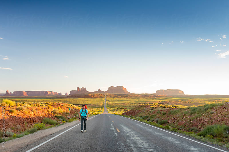 Backpacker Hiking at Mile 13 Forrest Gump Point on US 163 from Monument Valley Utah to Mexican Hat by JP Danko for Stocksy United