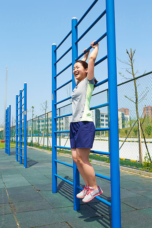 young asian woman stretch her body outdoor in the playground by cuiyan Liu for Stocksy United