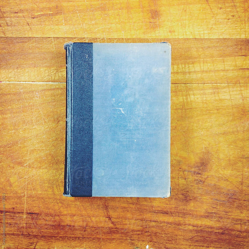 An old blue book lying flat on a wooden table. by Greg Schmigel for Stocksy United