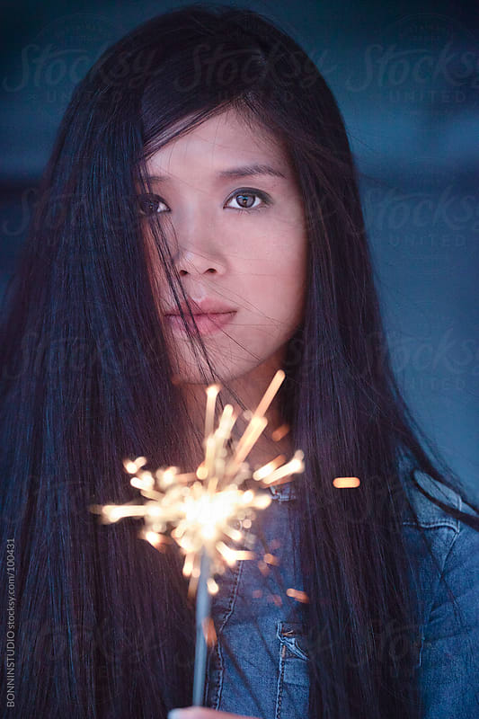 Asian woman with flying hair holding sparkler. by BONNINSTUDIO for Stocksy United