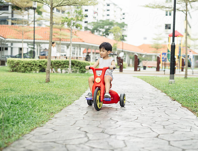 Little child cycling in the garden by Alita Ong for Stocksy United