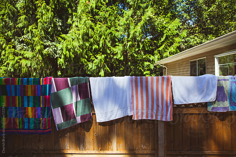 Colourful towels air dry on a fence in the summer sun. by Cherish Bryck for Stocksy United