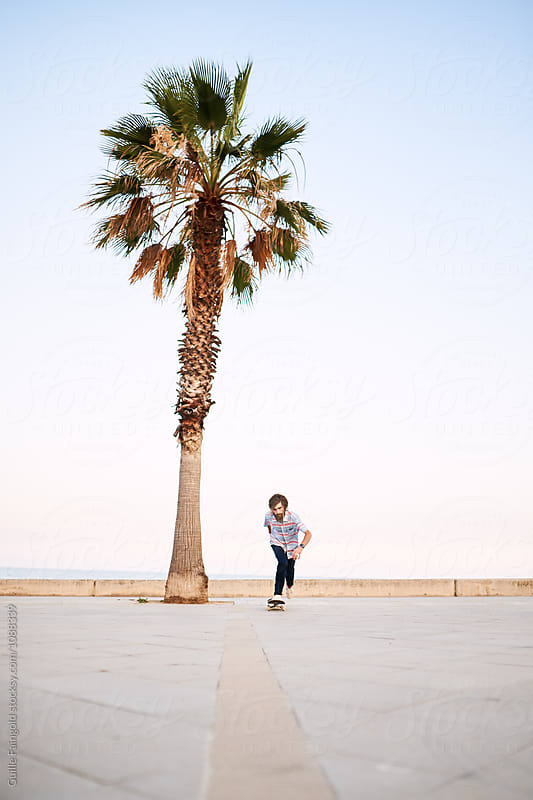 Bearded skater riding skateboard on road by Guille Faingold for Stocksy United