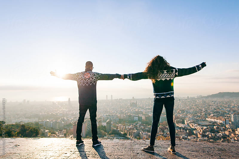 Back view of young couple having fun holding hands above Barcelona. by BONNINSTUDIO for Stocksy United