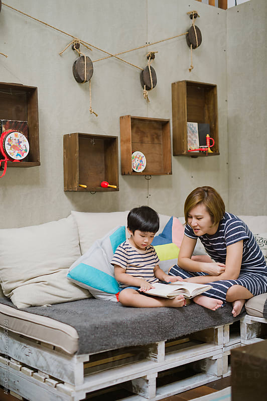 Family spending time in living room by Alita Ong for Stocksy United