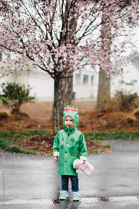Toddler in a raincoat playing in the rain by Jakob for Stocksy United