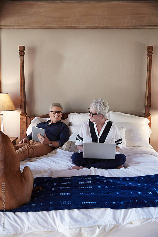 Mature couple with grey hair on the computer in bed with dog by Trinette Reed for Stocksy United