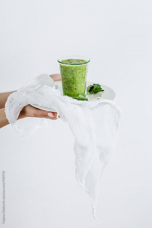 Hands holding green smoothie by Tatjana Zlatkovic for Stocksy United