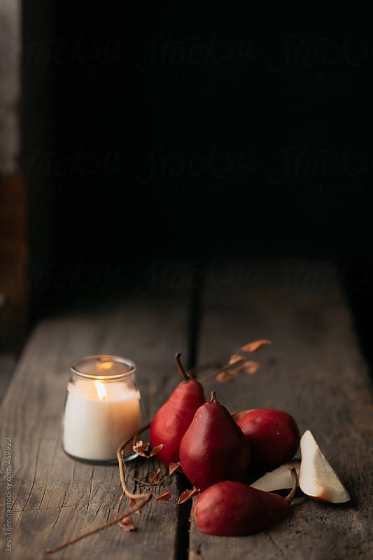 colorful cluster of pears on wooden farm table with candle by Levi Tijerina for Stocksy United