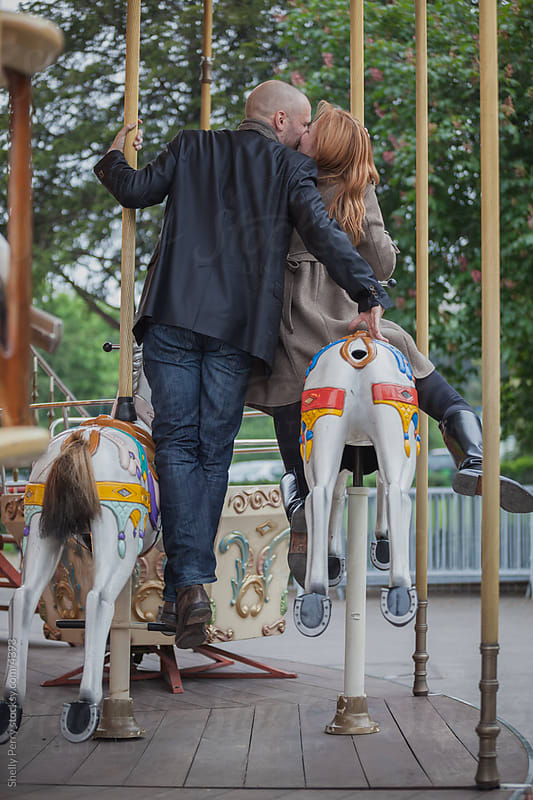 Romantic couple in Paris, kiss while riding a carousel by Shelly Perry for Stocksy United