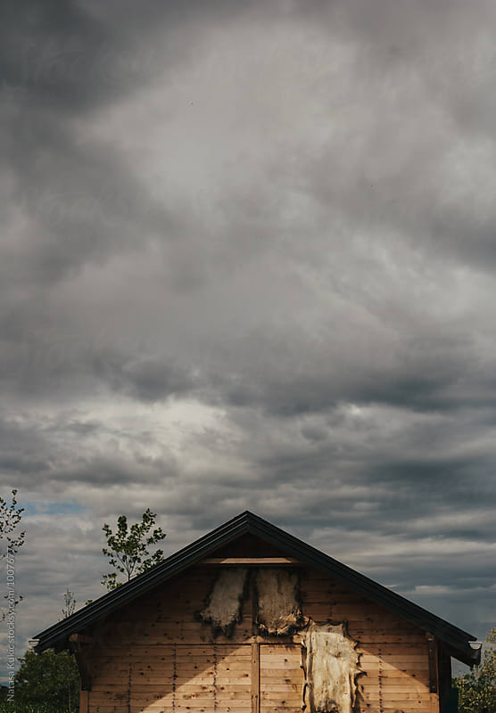 Top of the wooden cottage against the gloomy sky by Natasa Kukic for Stocksy United