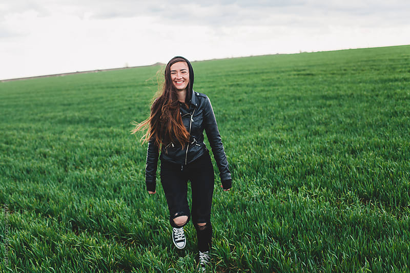 Sincere smile of a young woman in the countryside on green grass by paff for Stocksy United