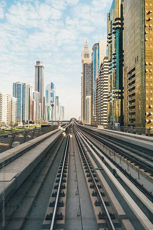 Railway and city buildings view in Dubai metro rail network. Dubai, United Arab Emirates by Alejandro Moreno de Carlos for Stocksy United