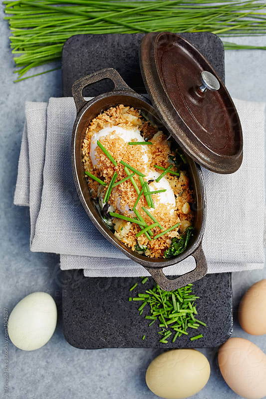 Breakfast casserole  of poached eggs, fontina cheese, chives, and truffles by Trinette Reed for Stocksy United
