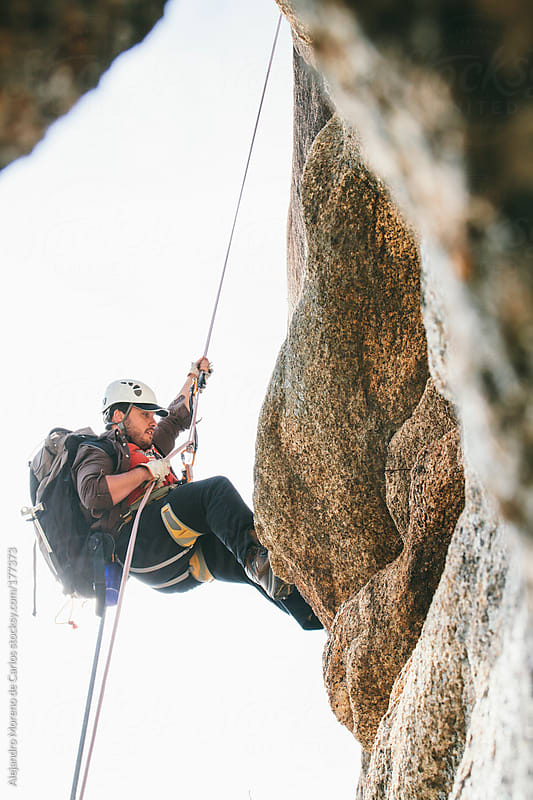 Man abseiling with rope after rock climbing  by Alejandro Moreno de Carlos for Stocksy United
